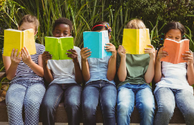 5 kids seating side by side, holding and reading books.